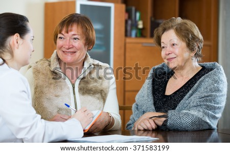 Professional female doctor consulting mature women in clinic interior  - stock photo
