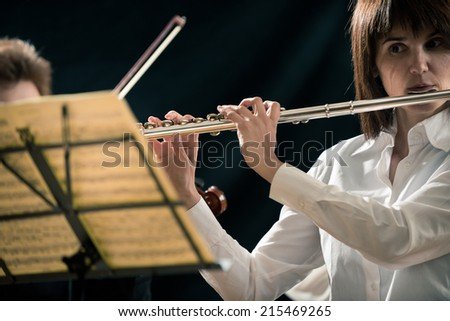 Professional female flutist performing on stage with sheet music. - stock photo