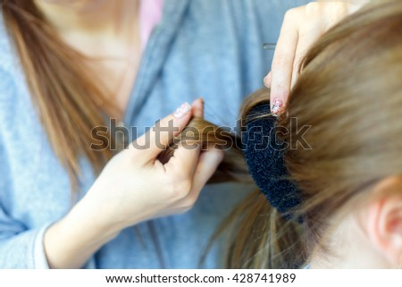Professional female hairdresser making hairstyle to cheerful young woman with long hair - stock photo