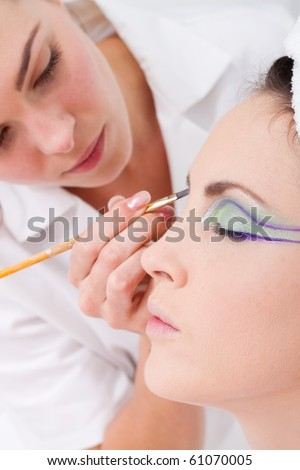 professional female makeup artist applying makeup to model's face - stock photo