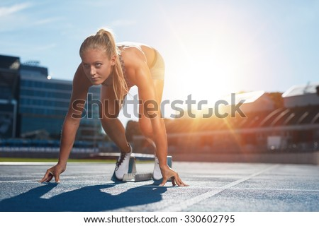 Professional female track athlete in set position on sprinting blocks of an athletics running track. Runner is in a athletics stadium with bright sunlight. - stock photo