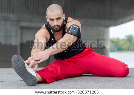 Professional fitness athlete trainer. Muscular male sportsman is training himself. Man is doing stretching. Outdoors fitness sport concept. Street flexibility workout in headphones - stock photo