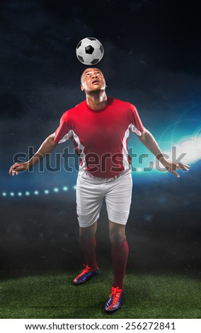 Professional football player balancing ball on his head - stock photo