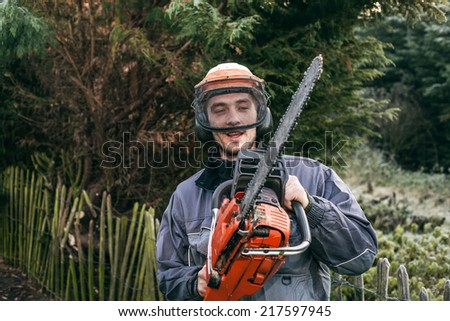 Professional gardener with chainsaw standing in the garden. - stock photo