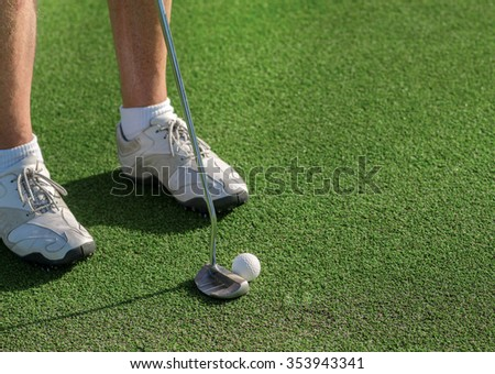 Professional Golf Course. Golfer holding a a club and is going to hit the golf ball. - stock photo