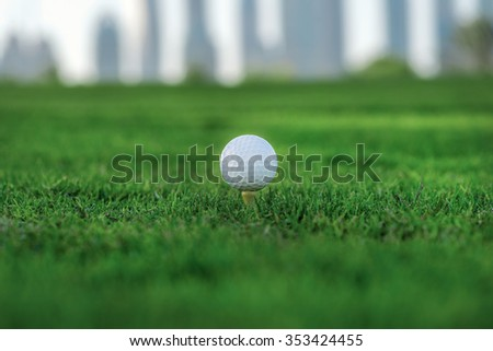 Professional golf. Golf ball is on the tee for a golf ball on the green grass of the golf course against the background the city skyscrapers - stock photo