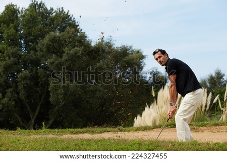 Professional golf player in action hitting golf ball, strong golf shot of handsome adult player standing on beautiful golf course - stock photo