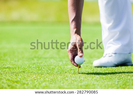 Professional Golf Player teach how to Teed Up Golf Ball - stock photo