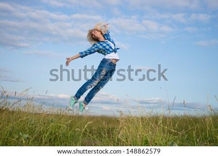 Professional gymnast woman jump in green grass field - stock photo