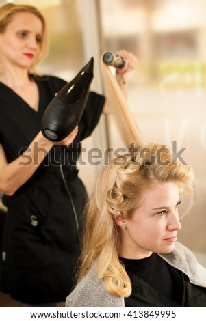 professional hair stylist at work - hairdresser  doing hairstyle to  beautiful young blonde customer in a professional studio - stock photo