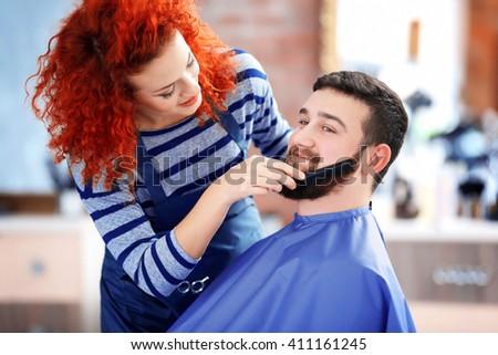 Professional hairdresser combing man beard - stock photo