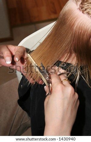 professional hairdresser cutting childs hair, preparing hair by combing it wet - stock photo