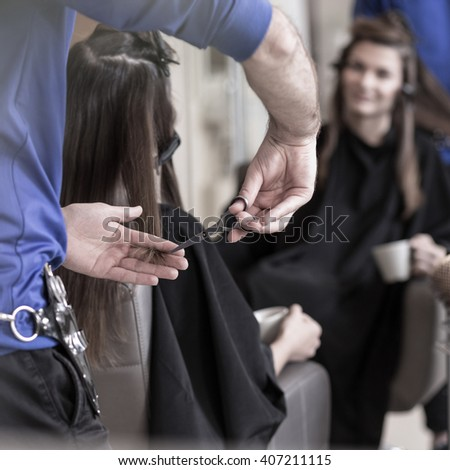Professional hairdresser doing a haircut to his client - stock photo