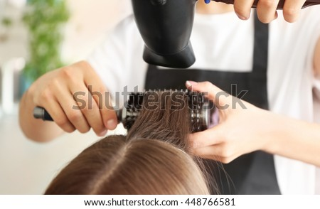 Professional hairdresser drying hair
