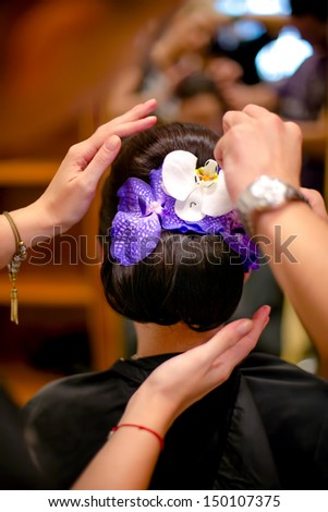 professional Hairdresser preparing a model and fixing a flower in hair for fashion event or wedding - stock photo