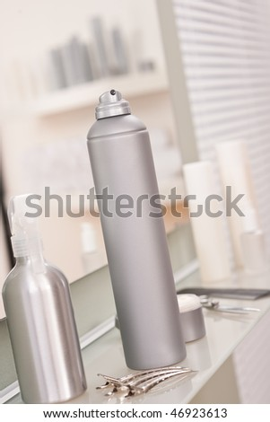 Professional hairdresser studio with hairspray and hair clip, reflection in mirror - stock photo
