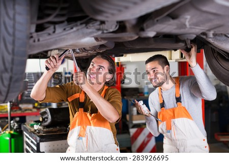 Professional happy young serviceman repairing car of client - stock photo