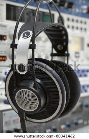 Professional headphones hanging in a recording studio in front of audio devices - stock photo