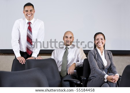 Professional Hispanic office workers sitting on chairs in boardroom by whiteboard - stock photo