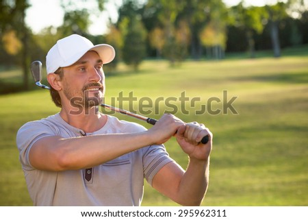 Professional image of a young male golf player. Golfer hitting driver club on course for tee shot. - stock photo