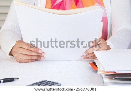 Professional in office reading through pile of documents - stock photo