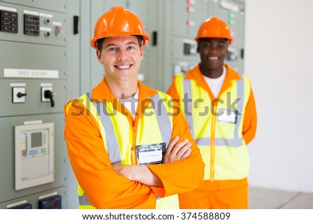 professional industrial electrician with colleague on background - stock photo