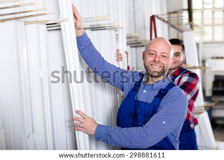 Professional industry workers are choosing white PVC window profiles inside a warehouse - stock photo