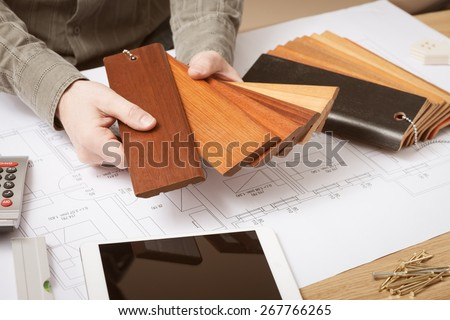 Professional interior designer holding wood swatches for baseboard and skirting, hands close up with desktop on background - stock photo