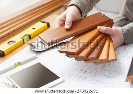 Professional interior designer holding wood swatches for baseboard and skirting, hands close up with desktop, house blueprint, tools and tablet - stock photo