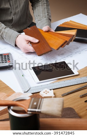 Professional interior designer holding wood swatches for baseboard and skirting, hands close up with desktop, house blueprint, tools and tablet on background - stock photo