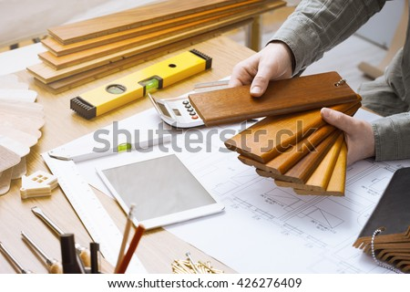 Professional interior designer holding wood swatches for baseboard and skirting, hands close up working at desk - stock photo