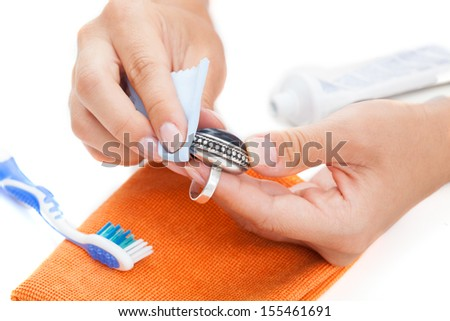 Professional jewellery cleaning with toothpaste and cleaning rug - stock photo