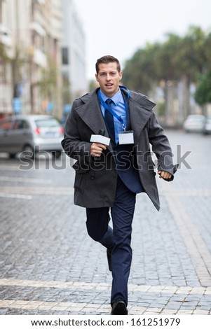 professional journalist running on urban street  - stock photo