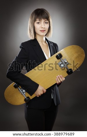 professional looking business woman holding a skateboard shot in the studio on a gray background low key lighting - stock photo