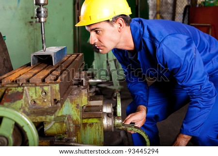professional machinist operating industrial drilling press - stock photo
