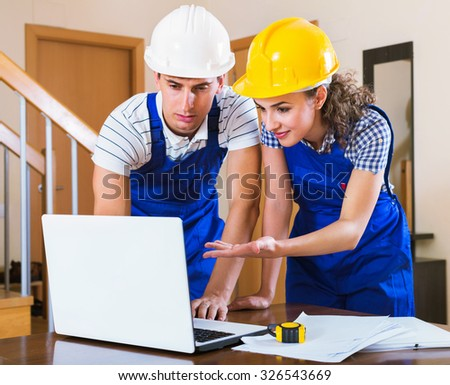 Professional  maintenance planner of two in yellow helmets indoors