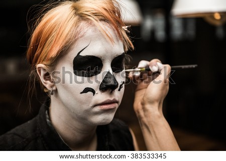 Professional make up artist applying halloween face paint close up