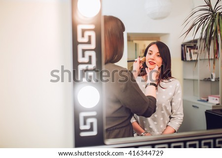 Professional make up artist applying make up to a fashion model / bride.