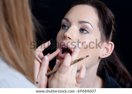 Professional make up artist applying make up to a fashion model/bride. - stock photo
