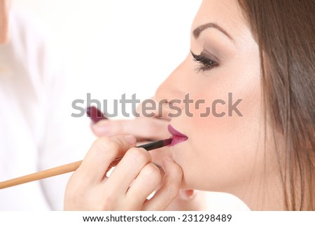 Professional Make-up artist doing beatiful girl makeup in studio - stock photo