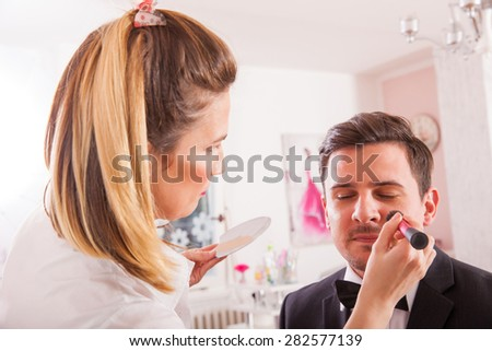 Professional Make-up artist doing young man makeup in studio - stock photo