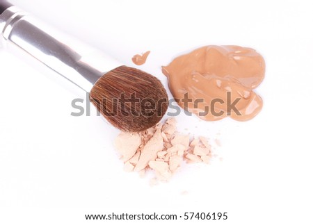 Professional make-up brush near crumbled eyeshadow and foundation, closed-up - stock photo