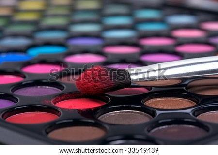 Professional make-up brush on color shadows in red participles - stock photo