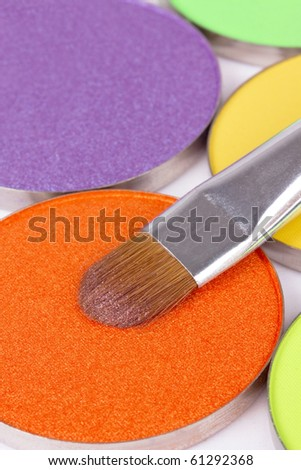 Professional make-up brush on orange eyeshadows palette, closed-up - stock photo