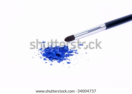 Professional make-up brush with blue damaged eye shadows isolated on white - stock photo
