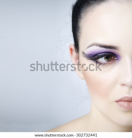 Professional makeup and hairstyle. Beautiful young woman close-up. Half face with copy space on a gray background