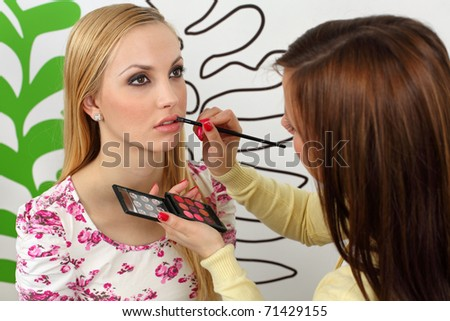 Professional makeup artist applying lipstick on attractive young woman lips. - stock photo
