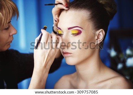 Professional makeup process. Artist is making face style of a young beautiful model at  blue studio background.