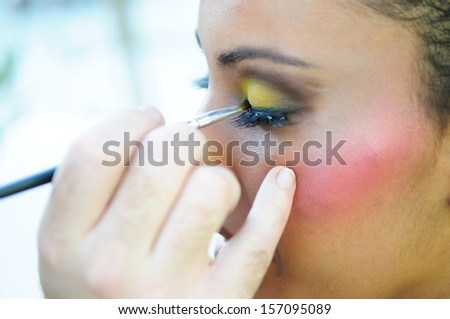 Professional makeup with a beautiful young black woman having touches applied to her make up by a beautician  - stock photo