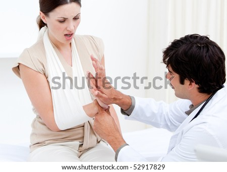 Professional male doctor examining the female patient by taking her arms in the hospital - stock photo